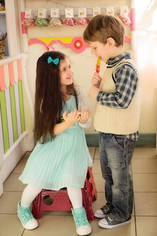 Meisje dat met tablet aan de jongen glimlacht