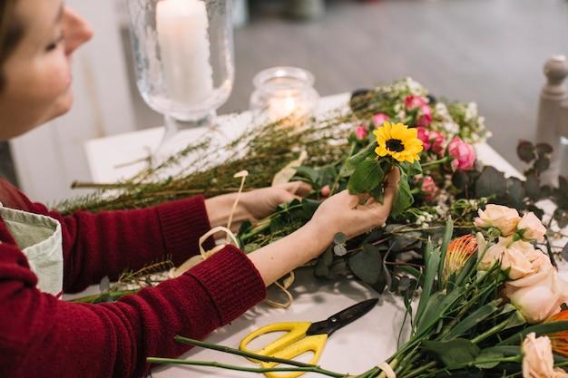 Meisje dat met verse bloemen werkt die boeket maken