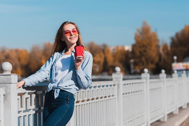 Meisje dat met zonnebril een kop van koffie houdt