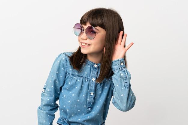 Meisje dat met zonnebril op witte muur wordt geïsoleerd die aan iets luistert door hand op het oor te leggen