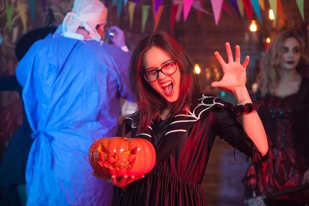 Meisje dat naar de camera schreeuwt, verkleed als een heks met een pompoen die halloween viert met haar vrienden.