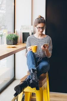 Meisje dat naar muziek op uw smartphone luistert en koffie drinkt