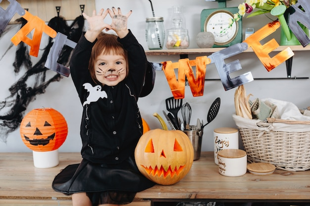 Meisje dat naast de pompoen zit en vuile wapens halloween toont