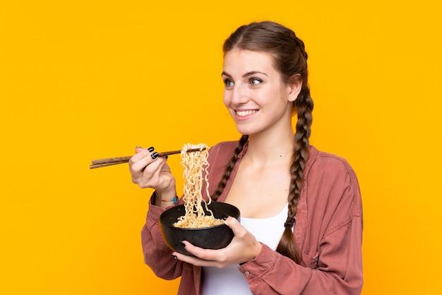 Meisje dat noedels over geïsoleerde gele muur eet
