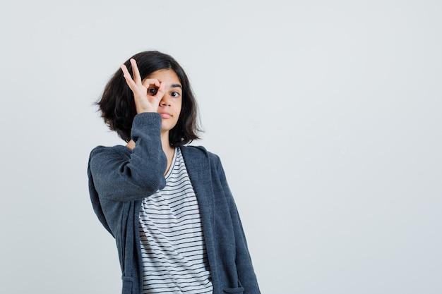 Meisje dat ok teken op oog in t-shirt, jasje toont en nieuwsgierig kijkt