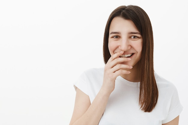 Meisje dat om je lacht terwijl je lol hebt en voor de gek houdt terwijl je in een speelse, vrolijke bui bent, giechelt, een perfecte glimlach bedekt met de hand en geamuseerd staarde terwijl hij poseert in een wit t-shirt tegen een grijze muur