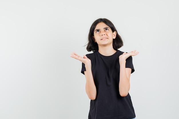 Meisje dat omhoog kijkt, dient zwarte t-shirt op en kijkt nieuwsgierig, vooraanzicht.