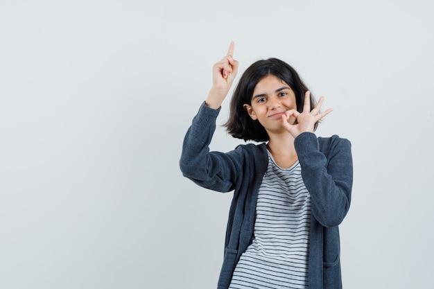 Meisje dat omhoog wijst, ok gebaar in t-shirt, jasje toont en vrolijk kijkt.