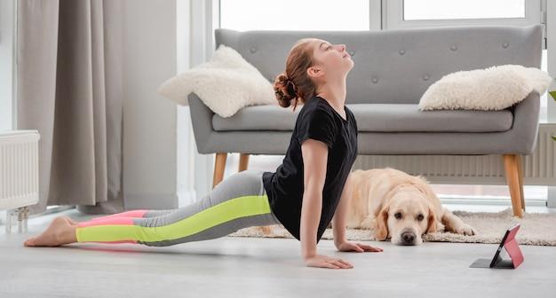 Meisje dat online yogatraining met tablet thuis in pandemische tijd en golden retrieverhond die haar bekijkt