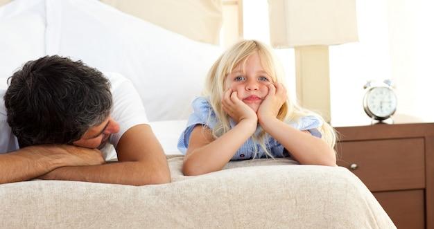Meisje dat op bed met haar vader ligt Premium Foto