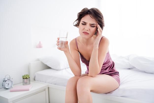 Meisje dat op bed zit en pillen slikt drugs voelt zich slecht
