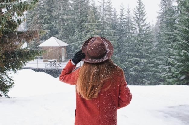Meisje dat op bergmening kijkt die hoed draagt