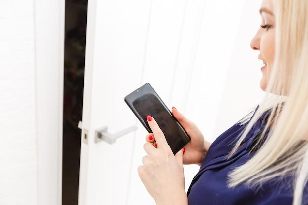 Meisje dat op de bank zit en een telefoon vasthoudt met het programma smart home op het scherm