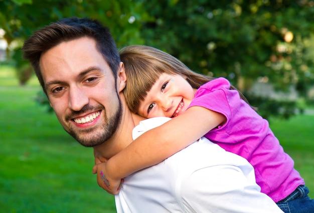 Meisje dat op de schouders van haar broer in het park loopt