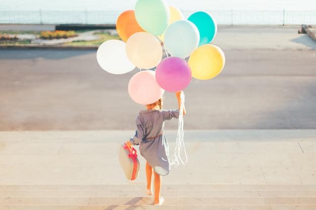 Meisje dat op de treden loopt die kleurrijke ballons en kinderachtige koffer houden