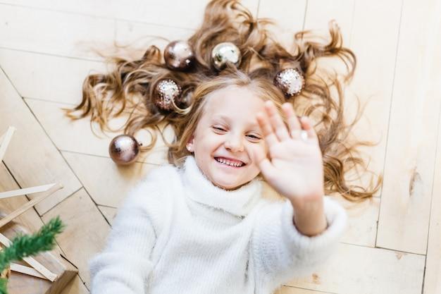 Meisje dat op de vloer in haar haarballen ligt voor kerstboom