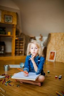 Meisje dat op de vloer ligt en met kleurpotloden trekt