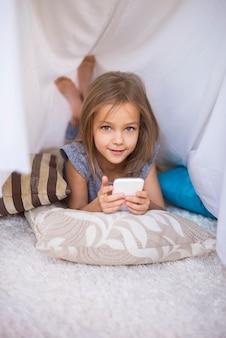 Meisje dat op de voorzijde ligt en een mobiele telefoon gebruikt