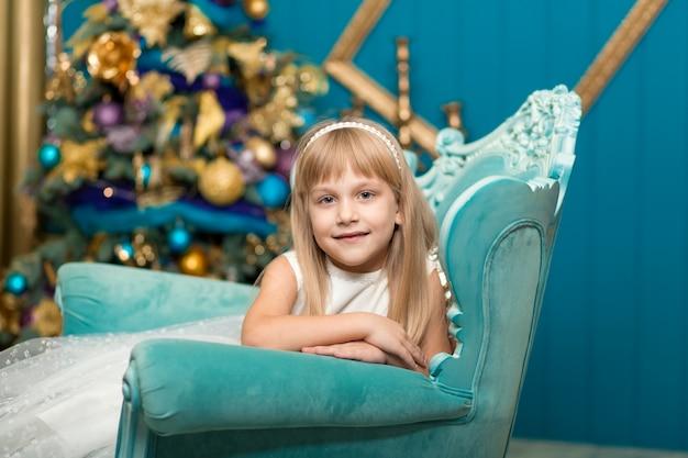 Meisje dat op een leunstoel dichtbij een kerstboom beweert te slapen om santa te ontmoeten wanneer hij cadeaus brengt.