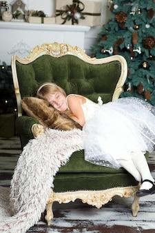 Meisje dat op een leunstoel dichtbij een kerstboom beweert te slapen om santa te ontmoeten wanneer hij cadeaus brengt