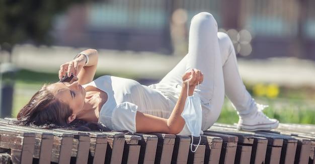 Meisje dat op een stadsbank ligt en haar mobiele telefoon gebruikt, met een gezichtsmasker in haar rechterhand.