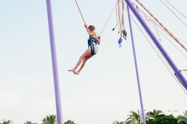 Meisje dat op een trampoline springt die door kabels bij een markt wordt geholpen.
