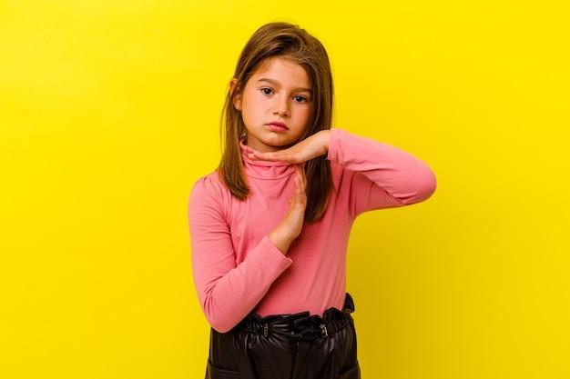 Meisje dat op gele muur wordt geïsoleerd die een time-outgebaar toont