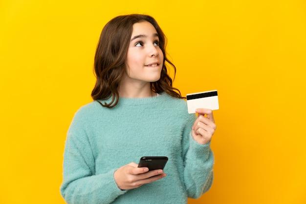 Meisje dat op gele muur wordt geïsoleerd die met mobiel met een creditcard koopt terwijl het nadenken