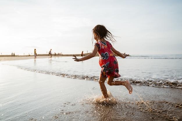 Meisje dat op het strand loopt terwijl het spelen met water