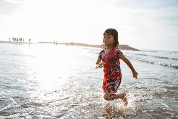 Meisje dat op het strand loopt terwijl het spelen van water