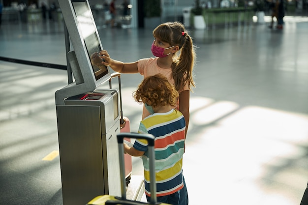 Meisje dat op knoppen drukt op een scherm voor het neerzetten van een tas