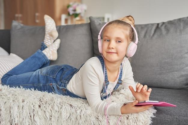 Meisje dat op laag in hoofdtelefoons legt, die aan muziek met haar smarthphone luistert