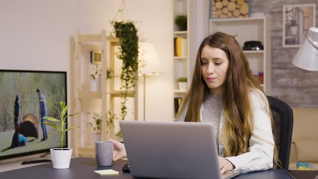Meisje dat op laptop werkt vanuit kantoor aan huis. meisje dat een slokje koffie neemt.