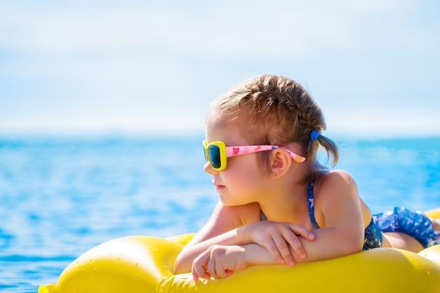 Meisje dat op opblaasbare strandmatras zwemt.