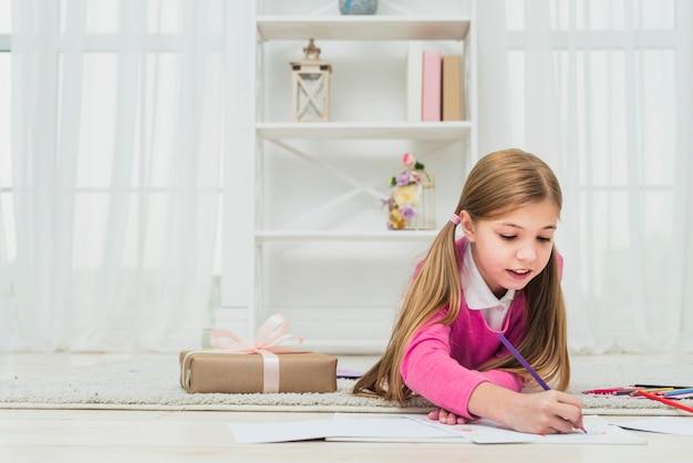 Meisje dat op papier dichtbij giftdoos trekt