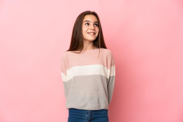 Meisje dat op roze achtergrond wordt geïsoleerd die een idee denkt terwijl het opzoeken