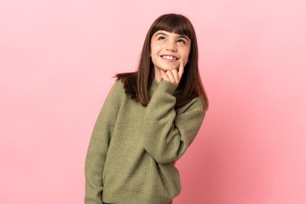Meisje dat op roze muur wordt geïsoleerd die een idee denkt terwijl het opzoeken