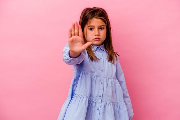 Meisje dat op roze muur wordt geïsoleerd die zich met uitgestrekte hand bevindt die stopbord toont, dat u verhindert