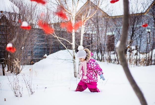 Meisje dat op sneeuw in de winter, dorp of tuin, sneeuw en bomen loopt.