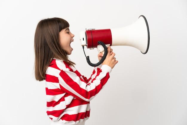 Meisje dat op witte muur wordt geïsoleerd die door een megafoon schreeuwt om iets in zijpositie aan te kondigen