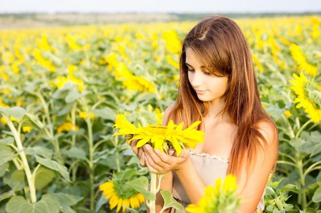 Meisje dat op zonnebloemgebied een zonnebloemhoed houdt