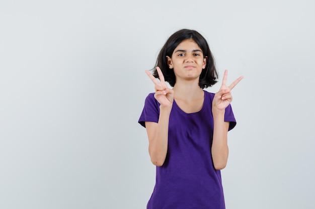 Meisje dat overwinningsteken in t-shirt toont en zelfverzekerd kijkt.