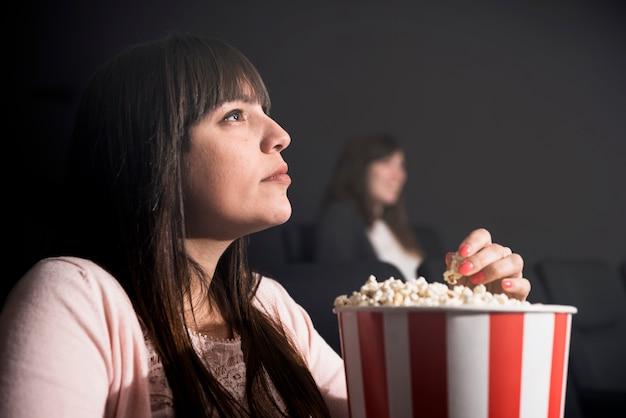 Meisje dat popcorn in bioskoop eet