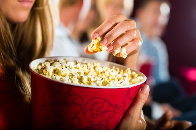 Meisje dat popcorn in bioskoop of bioscoop eet