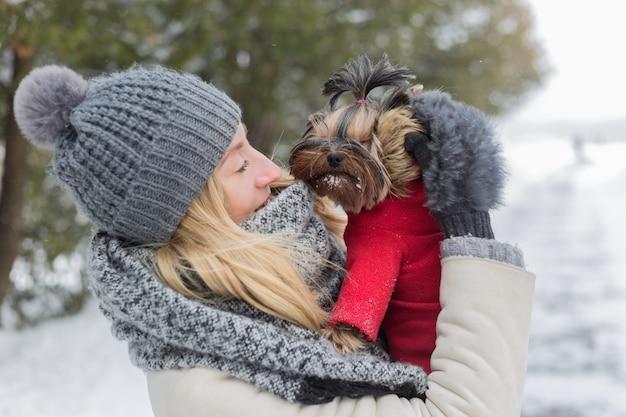 Meisje dat pret buiten in sneeuw met haar hond yorkshire terrier heeft.