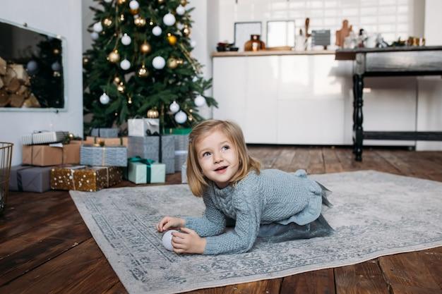 Meisje dat pret heeft dichtbij kerstboom in de ochtend