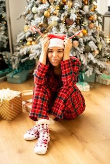 Meisje dat pret heeft en kerstmis viert. ze liet haar tong zien om te lachen. op de achtergrond versierde kerstboom met cadeautjes.