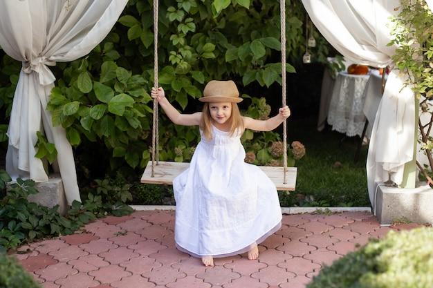 Meisje dat pret op een schommeling in mooie de zomertuin in openlucht heeft op warme en zonnige dag. actieve zomervakantie voor kinderen