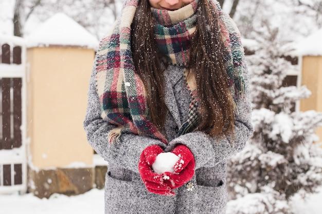 Meisje dat rode behandelde handschoenen draagt die sneeuw met vrolijke kerstmisgroet houden