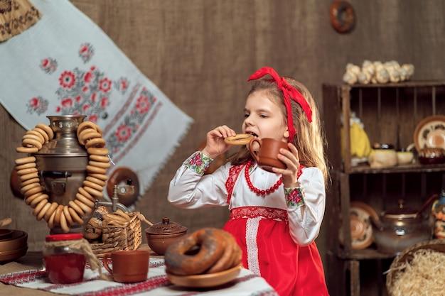 Meisje dat rode hoofdband en sieroverhemd het drinken thee van samovar draagt die maslenitsa viert
